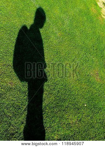 Long Shadow Of Child On Green Grass