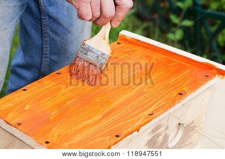 Worker Adds Protective Covering With Brush On Wood