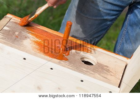 Worker Adds Red Protective Covering With Brush