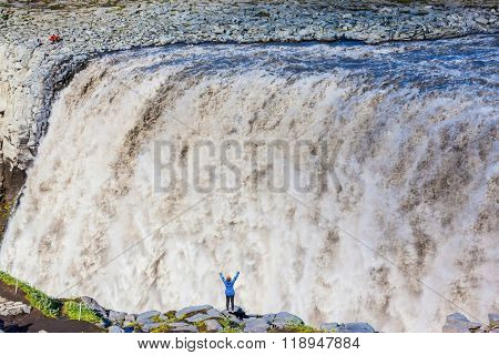 Colossal roaring waterfall Dettifoss. Elderly woman admires the picturesque spectacle. Huge masses of water cascading into the abyss. Iceland, Jokulsargljufur National Park