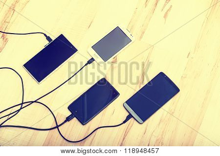four smartphones connected to chargers. wooden floor