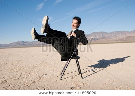 Laughing businessman sitting on a chair