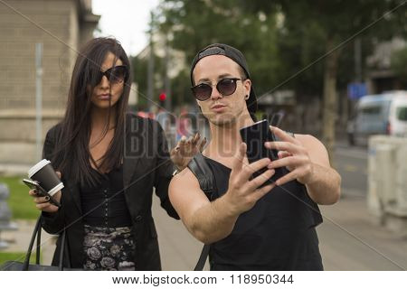 Young cheerful friends taking photos of themselves on smart phone, urban city outdoor scene, selective focus
