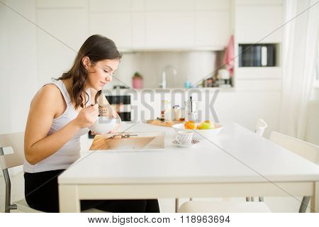 Young brunette is reading the newspaper while having breakfast at home.Modern woman healty breakfast