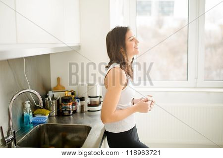 Modern working woman lifestyle-drinking coffee or tea in the morning in the kitchen,starting day