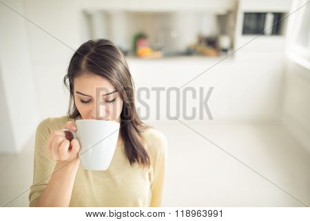 Young woman enjoying,holding cup of hot beverage,coffee or tea in morning sunlight