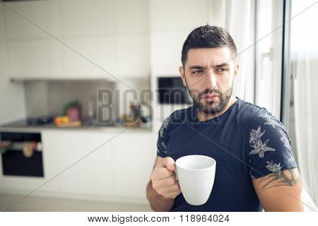 Man holding cup of hot beverage,coffee or tea.Enjoying his morning coffee in the kitchen.Looking tro