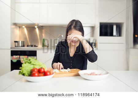 Young housewife beginner cook crying while cutting onion.Slice,dice and choped onion