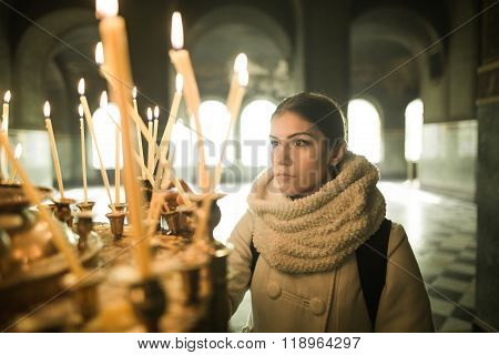 Young female lighting candles in a church during praying.Yellow votive candles burning