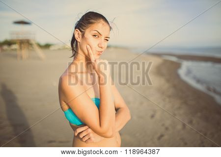 Thinking woman standing pensive contemplating looking skeptic. Judgmental summer beach woman expressing confusion and distrust. Young brunette looking curious, evaluating something
