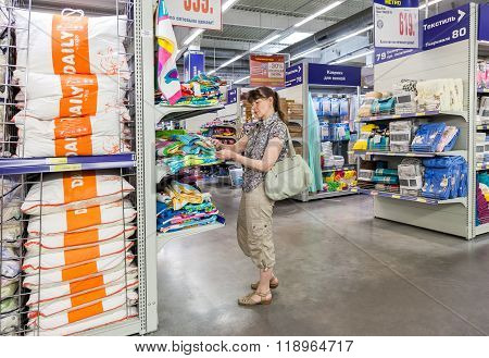 Young Woman Choosing Bedclothes At Shopping In Hypermarket Metro