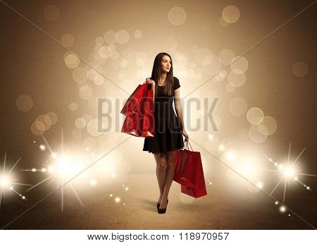A beautiful elegant woman in black standing with red shopping bags in front of brown background and bright glowing lights concept