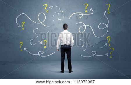 A salesman in doubt can not find the solution to the problem concept with curvy lined arrows and question marks drawn on urban wall