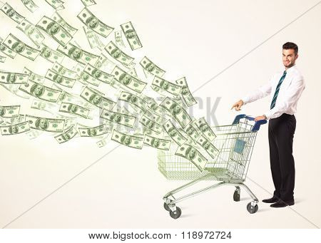 Businessman pushing a shopping cart and dollar bills coming out of it