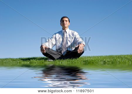Businessman meditating on green grass