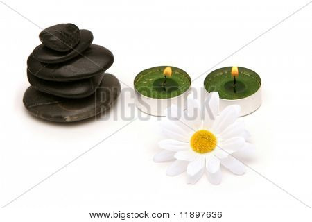 Massage stones, candles and daisies on white background