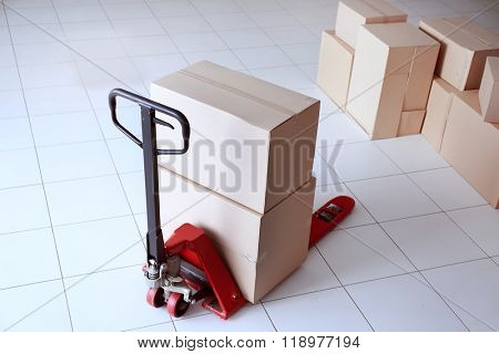 Fork pallet truck with stack of cardboard boxes indoors