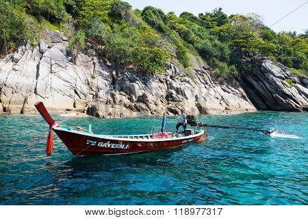 PHI PHI ISLANDS, THAILAND - CIRCA FEBRUARY, 2015: Traditional Thai boat on the shore of the island of Phi Phi Islands in the Andaman Sea. Islands is very popular with tourists from all over the world