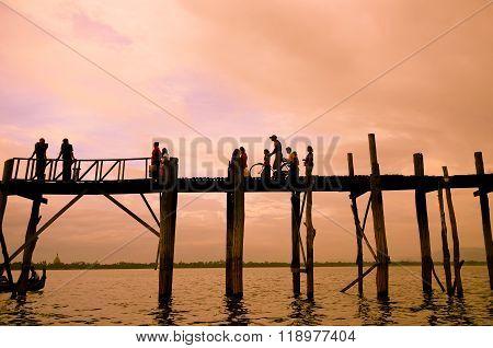 MANDALAY - September 2, 2013 : Monks walking on U-Bein bridge in sunset, Mandalay, Myanmar. The U-Bein bridge is the longest teak bridge in the world