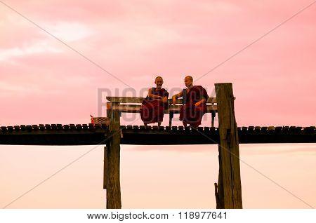 MANDALAY - September 2, 2013 : People walking on U-Bein bridge in sunset in Mandalay, Myanmar. The U-Bein bridge is the longest teak bridge in the world