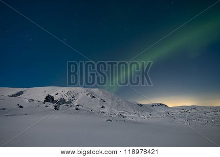 Northern lights in the sky over snow covered mountains