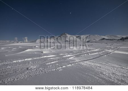 Starry sky over snow covered mountains in the wintertime