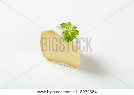 slice of white rind cheese with parsley on white background