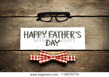 Happy Father's Day inscription with red bow tie and glasses on wooden background. Greetings and presents