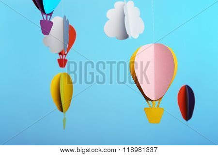Paper clouds and airship on blue background