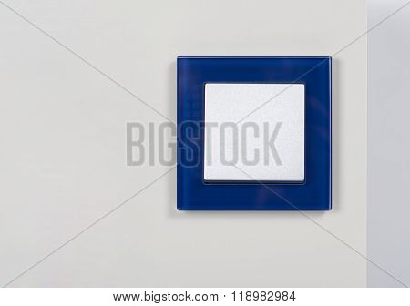 Light Switch With Blue Glass Frame On The Wall