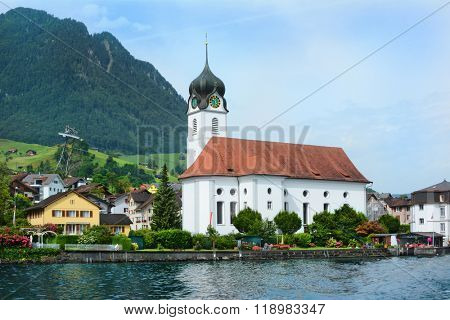 BECKENRIED, SWITZERLAND - JULY 4, 2014: St. Heinrich Church in Beckenried on the banks of  Lake Lucerne. Beckenried is a town in the canton of Nidwalden.
