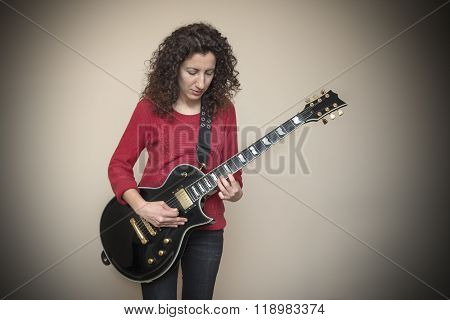 Woman Playing Black Electric Guitar