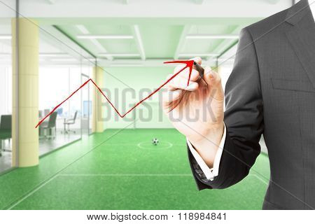 Man Paints Red Arrow Up On Glassy Wall In Modern Office With Footbal Field