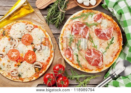 Pizza with prosciutto and mozzarella and with tomatoes and mushrooms on wooden table. Top view