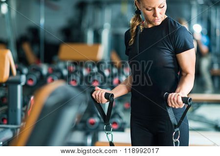 Female Athlete Exercising In The Gym Using Trx