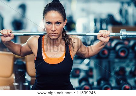 Woman Exercising In Gym With Olympic Barbell Weights