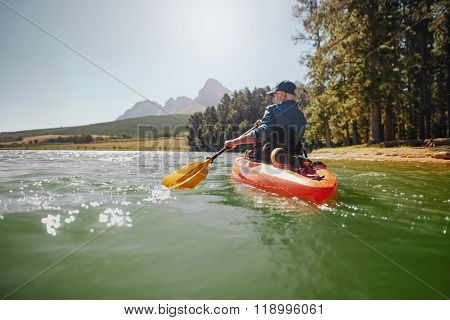 Senior Man Paddling Kayak On A Summer Day