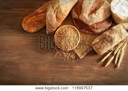 Fresh baked bread and a bowl of wheat grains on the wooden background