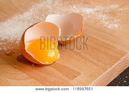 Close up egg, yolk in eggshell, flour on a wooden background