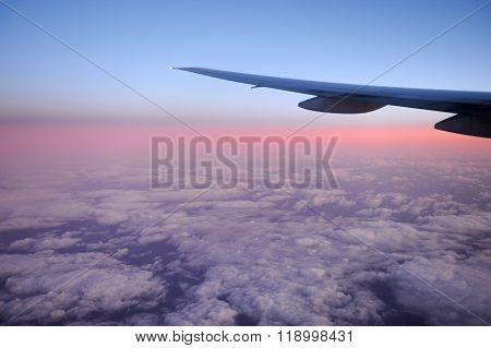 pink dawn light on the cloud under the airplane wing