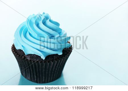 Chocolate cupcake on blue background