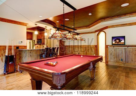 Large Hardwood Floor Room With Pool Table And Bar.