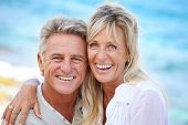 stock photo of maturity  - Happy mature couple smiling and embracing outdoors - JPG