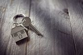 House key on a house shaped keychain resting on wooden floorboards concept for real estate, moving h poster