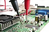 picture of multimeter  - Multimeter probes examining a computer circuit board - JPG