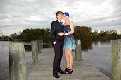 Young teen couple pose for prom photo on pier near river. poster