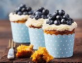 Pumpkin cupcakes decorated with cream cheese frosting and fresh blueberries on a wooden background poster