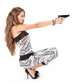 image of harem  - Young woman in harem pants aiming with black pistol on white - JPG