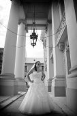 Young bride posing for the camera in front of large columns