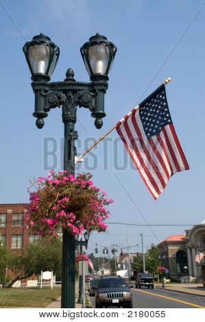 Lamppost With Flag And Flowers